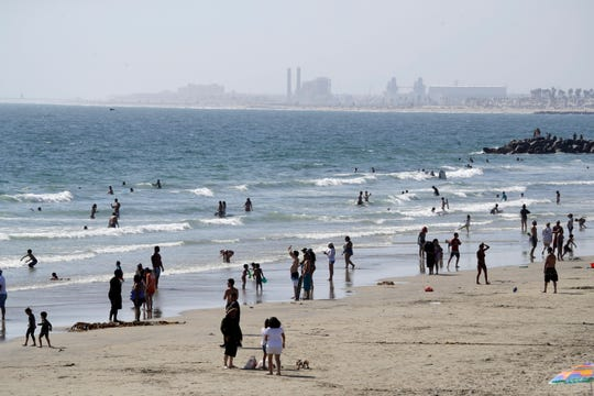 People visit the beach May 24 in Newport Beach, Calif.