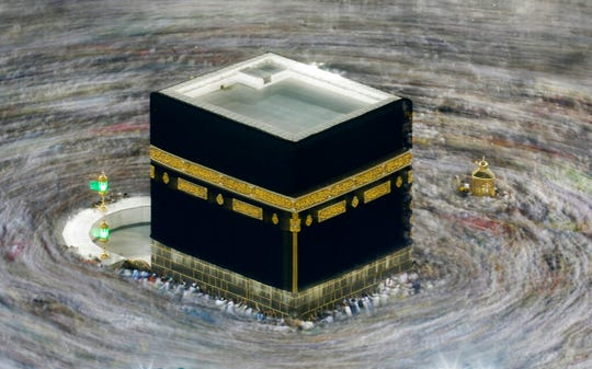 """In this Aug. 13, 2019 file photo taken with slow shutter speed, Muslim pilgrims circumambulate the Kaaba, the cubic building at the Grand Mosque, during the hajj pilgrimage in the Muslim holy city of Mecca, Saudi Arabia. Saudi Arabia says this year's hajj will not be canceled, but that due to the coronavirus only """"very limited numbers"""" of people will be allowed to perform the major Muslim pilgrimage."""
