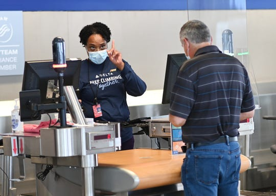 Delta Airlines customer service agent Monica Miller wears a protective mask and is guarded by a plastic shield as she assist a customer inside the McNamara Terminal at Detroit Metropolitan Wayne County Airport in Romulus.