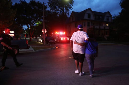 Two people walk away from West Suburban Medical Center in Oak Park, in Chicago, where a 3-year-old boy died after being shot while riding in an SUV with his father a few blocks away in the Austin neighborhood, Saturday, June 20, 2020.