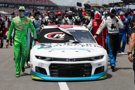 Nascar drivers Kyle Busch, left, and Corey LaJoie, right, join other drivers and crews as they push the car of Bubba Wallace to the front of the field prior to the start of the NASCAR Cup Series auto race at the Talladega Superspeedway in Talladega Ala., Monday June 22, 2020.