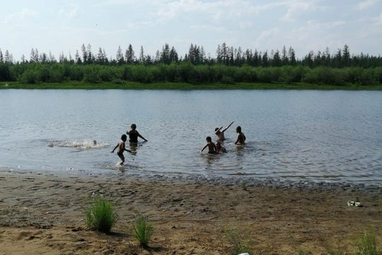 Children play in the Krugloe lake outside Verkhoyansk, the Sakha Republic, Sunday, June 21, 2020. A Siberian town that endures the world's widest temperature range has recorded a new high amid a heat wave that is contributing to severe forest fires.