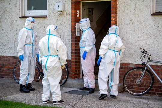Members of German Red Cross (DRK) stand in front of a house where employees of the Toennies meat factory live in Rheda-Wiedenbrueck, Germany, Monday, June 22, 2020. About 40 mobile test teams are on the road that day to visit employees of the Toennies company at home in their quarantine.