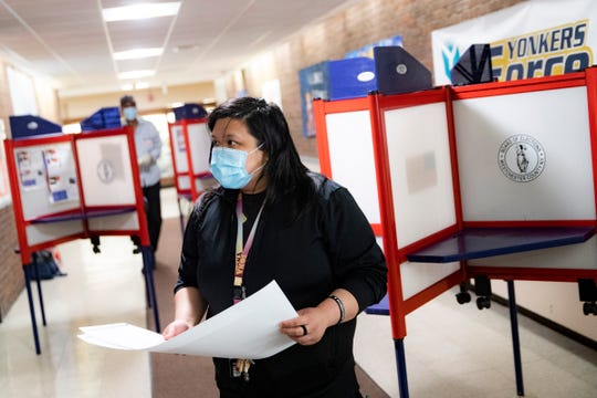 A voter wears a protective mask while casting their vote in New York's primary election at a polling site inside Yonkers Middle/High School, Tuesday, June 23, 2020, in Yonkers, N.Y.