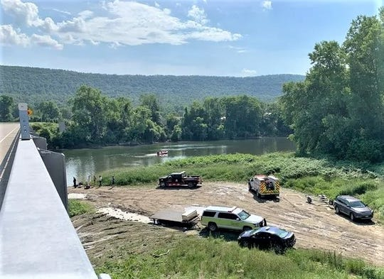 Emergency responders gather Monday along the Chemung River in the Town of Chemung after a kayak carrying three women capsized.