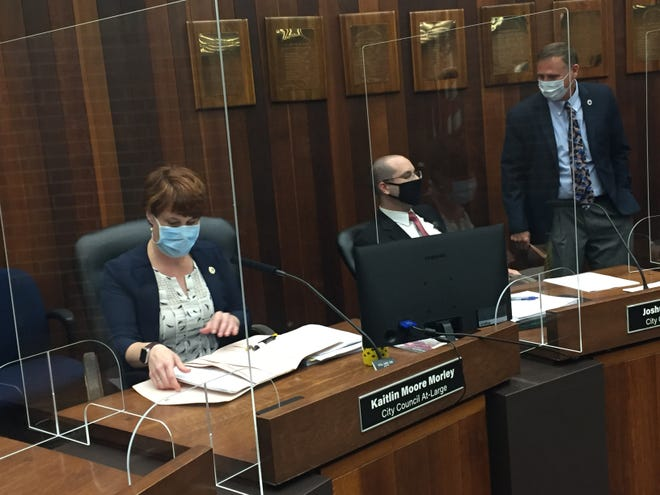Back in the Civic Center for the first time since mid-March, the Evansville City Council prepared for its meeting Monday night with facemasks and new plexiglass shields at their desks. From left: Councilor Kaitlin Moore, City Council Attorney Joshua Claybourn and Councilor Jim Brinkmeyer.