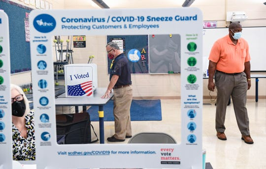 Frank Cox, left, votes at University Precinct near poll manager Ray Brown during Pickens County runoff elections in Clemson, S.C.  The City Council in Greenville voted Monday to require people to wear masks in grocery stores and pharmacies, becoming the first in the state mandating face coverings to fight COVID-19.