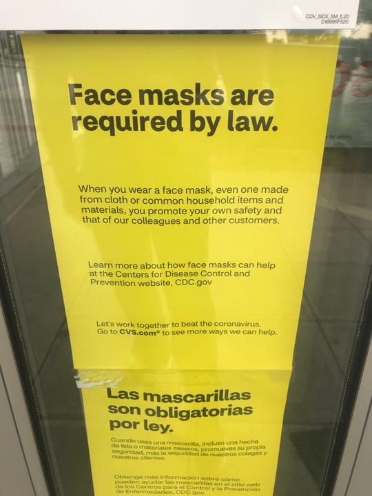 A sign on the door of CVS Pharmacy on Main Street in Greenville the day the city's new face mask requirement went into effect.