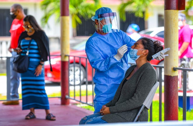A nasal swab sample is collected from an individual during an extended COVID-19 outreach by the Department of Public Health and Social Services and other health care professionals near the Barrigada Mayor's Office in this June 23 file photo.