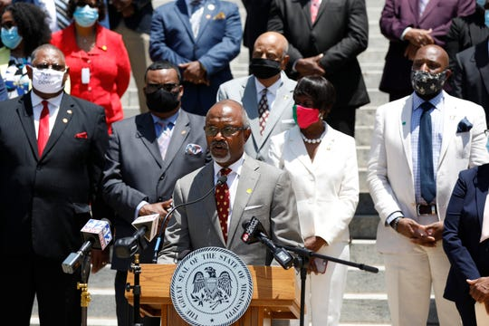 Rep. Robert Johnson, D-Natchez, Democratic leader of the House and flanked by party lawmakers and members of the Mississippi Legislative Black Caucus, stands at the podium and says the state flag does not unify Mississippi, and calls on the Legislature to vote for a new flag this session, during a news conference in front of the Capitol in Jackson, Miss., Tuesday, June 23, 2020. (AP Photo/Rogelio V. Solis)