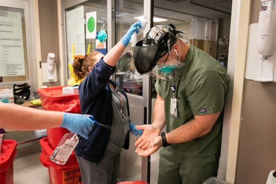 Shannon Moffett, University of Mississippi Medical Center pulmonary nurse practitioner, cleans the face shield of Kevin Marchant, an MICU nurse, as another team member sprays his hands with alcohol.