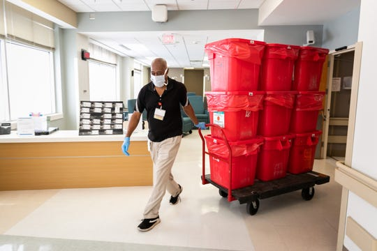 Housekeeper Bill Culpepper pulls a dolly laden with nine hazardous waste containers holding soiled and contaminated personal protective equipment and medical supplies from the medical ICU at the University of Mississippi Medical Center.