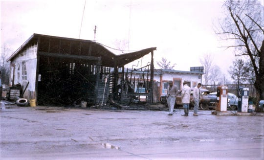 "Anthony ""Lucky"" McCraney (white coat, rubber boots), a member of the Ferriday Deacons chapter, surveys his service station after it was firebombed by the Klan in 1965."