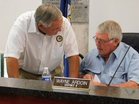 St. Landry Parish Council members Harold Taylor (left) and Wayne Ardoin talk during the start of a public hearing for several ordinances considered during a monthly council meeting.