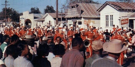 A homecoming parade for Ferriday's black Sevier High moves down the main road through town in 1962. At far left (behind the tuba) on opposite side of the street is Frank Morris' shoe shop two years before it was torched.