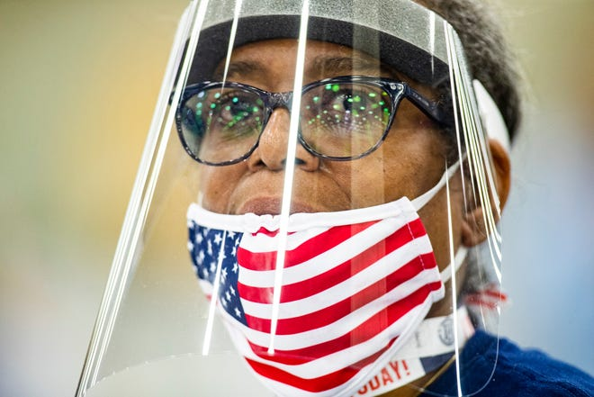 Wanda Wilson wears an American flag mask and face protection while handing out ballots during Kentucky's primary voting on election day at the Kentucky Expo Center. June 23, 2020