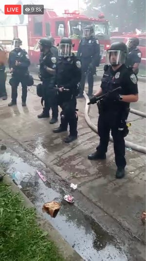 Police stand near the scene of a fire at North 40th and West Lloyd streets, seen in protest organizer Frank Nitty's livestream.