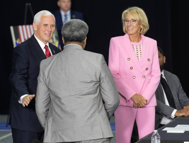 Vice President Mike Pence, left, greets Calvin A. Lee, of the American Federation for Children, while accompanied by Education Secretary Betsy DeVos before a school choice roundtable discussion Tuesday, June 23, 2020 at the Waukesha STEM Academy, 130 Walton Ave. in Waukesha, Wis.