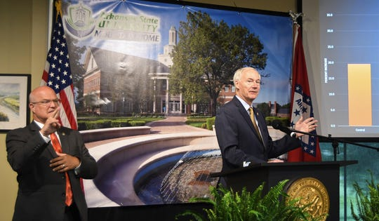 Asa Hutchinson (right) speaks at Tuesday's COVID-19 news conference while interpreter Eddie Schmeckenbecher signs the governor's comments on Tuesday.