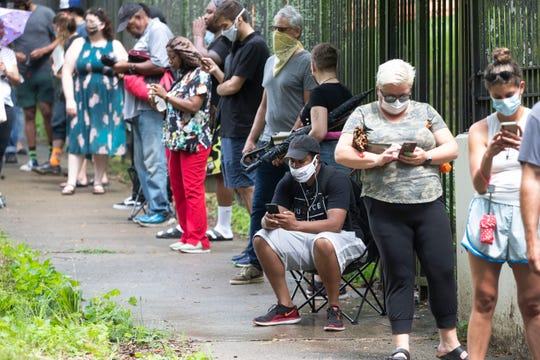 FILE - In this June 9, 2020, file photo, Steven Posey checks his phone as he waits in line to vote at Central Park in Atlanta. Voters reported wait times of three hours. When some Georgia voters endured a pandemic, pouring rain and massive waits earlier this month to cast their ballot, President Donald Trump and other Republicans blamed local Democrats for presiding over chaos. (AP Photo/John Bazemore, File)