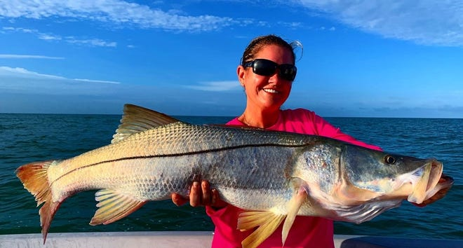 Kacey Farmer shows a snook she caught on the rocks off Doctors Pass in Naples.