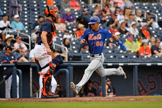New York Mets shortstop Andres Gimenez (60) scores a run in the second inning of the spring training game against the Houston Astros at FITTEAM Ballpark of the Palm Beaches.