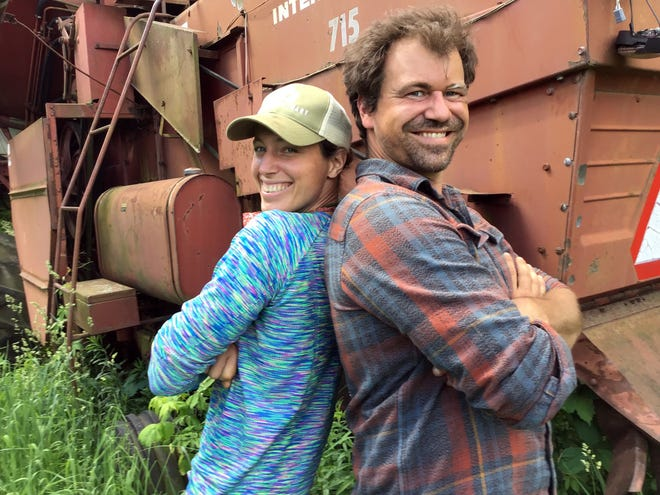 Helen Chandler and Jim Neumann slow down long enough to pose for a portrait in front of a piece of farm machinery abandoned by a previous owner.