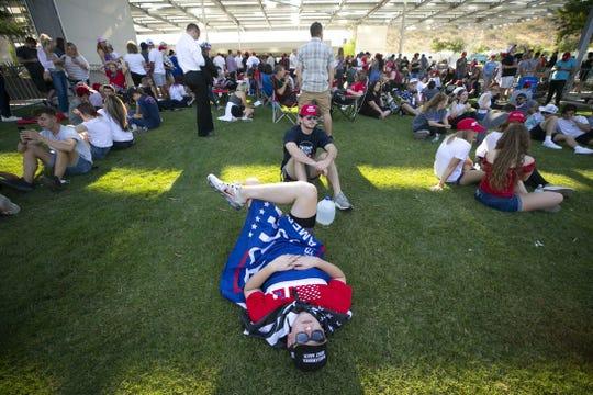"""El partidario de Trump, Jake Eaker, de 18 años, de Gilbert, descansa en el suelo mientras espera ingresar a Dream City Church antes del evento """"Estudiantes para Trump"""", donde el presidente Donald Trump hablará en Dream City Church en Phoenix el 23 de junio de 2020."""
