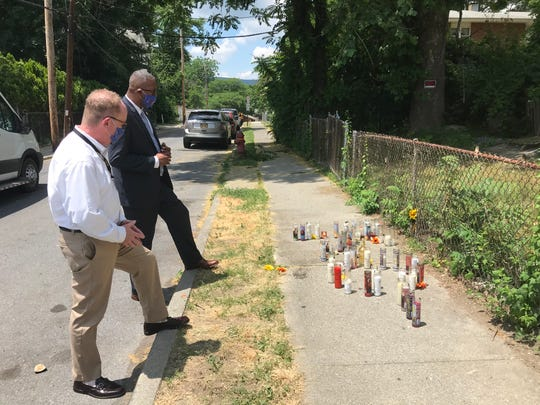 City of Poughkeepsie Mayor Rob Rolison, left, and Poughkeepsie City School District Superintendent Eric Jay Rosser Tuesday pause in front of a memorial for a 16-year-old shooting victim on Charles Street.