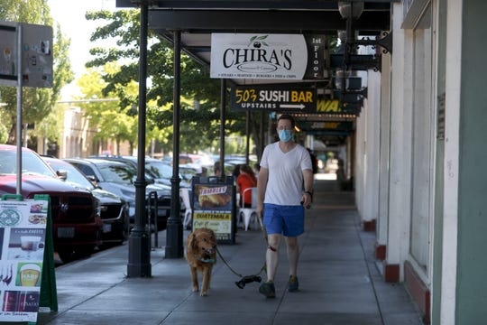 An individual wearing a mask walks a dog in downtown Salem along Liberty St NE, on Monday, June 22, 2020.