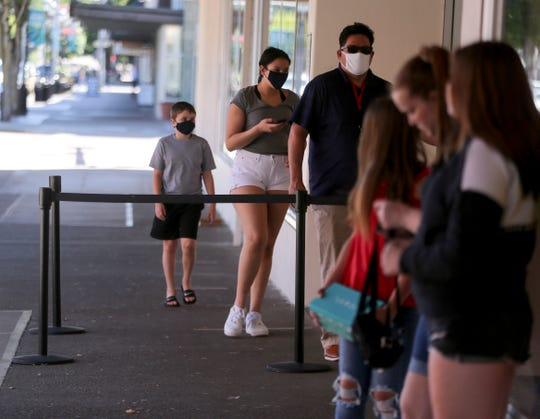 A family wearing masks enters JC Penney as an unmasked group stands outside in Salem, Oregon, on Monday, June 22, 2020.