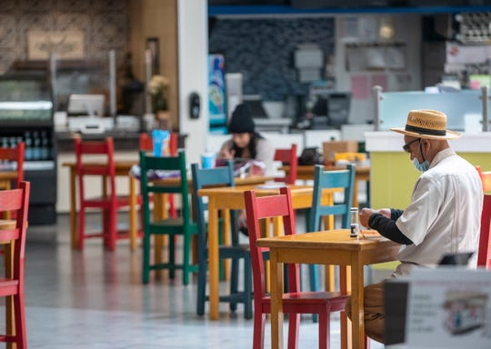 People practice social distancing at the food court inside Northridge Mall amid a spike in COVID-19 cases in June 2020.