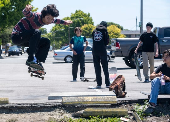 A group of boys skate in the Winchell's parking lot in south Salinas, Calif. amid a spike in COVID-19 cases in June 2020.