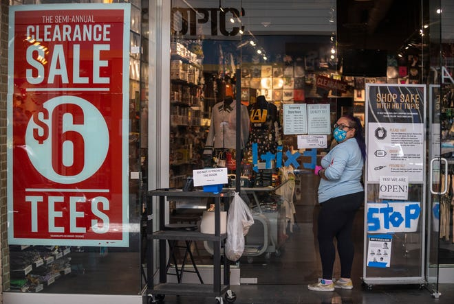 A woman wearing a face mask stands outside Hot Topic in the Northridge Mall in June 2020.