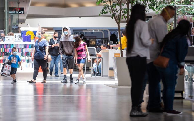 A family wearing blue surgical face masks walks through the Northridge Mall in Salinas, Calif. amid a rise in COVID-19 cases in June 2020.