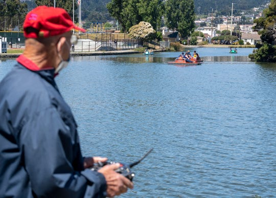 A man wearing a face mask uses a remote control to operate his mechanical boat on El Estero Lake in Monterey, Calif., in June 2020. People have been practicing social distancing at varying levels amid a spike in COVID-19 cases.