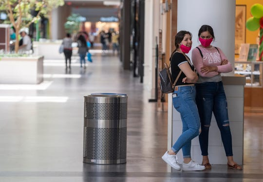 Two women stand close wearing face masks amid the spike in COVID-19 cases in June 2020.