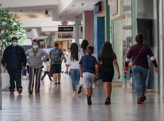 Groups of people shop at the Northridge Mall amid a spike in COVID-19 cases in June 2020. Some are wearing face masks while others are not.