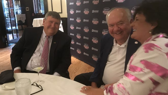Radiance Technologies CEO Bill Bailey shares a laugh with 2020 Radiance Technologies Independence Bowl chairman Frank Auer and his wife, Gail.