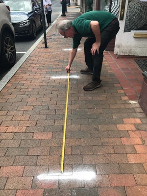 Benjamin Roe, director of Heifetz Institute, measures painted white dashes that appeared on the sidewalks along Beverley Street and in front of the Heifetz store. They are six feet apart to encourage physical distancing as people arrive at the courthouse.