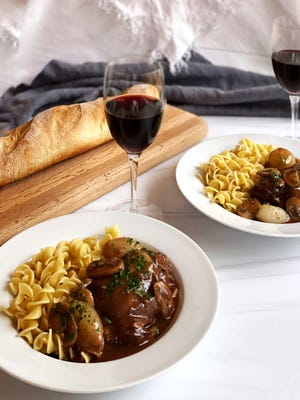 Coq au Vin is a classic French dish of chicken cooked in red wine with onions, carrots, garlic, mushrooms and fresh herbs.