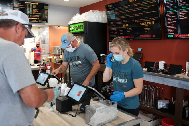 Roger Rankin, left, and Peyton Eldridge take orders during Tuesday's lunch rush at Rankin Tacos.