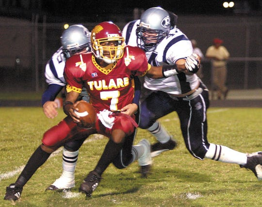 Tulare Union's quarterback Emmanuel Lewis tries to evade Redwood's Bo Pina, left, and Max Navo during the first half of Friday's Homecoming game at Bob Mathias Stadium, Oct. 3, 2003.