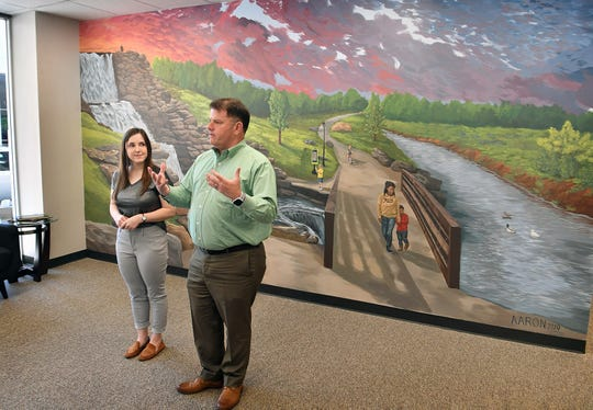 Henry Florsheim, president of the Wichita Falls Chamber of Commerce, introduces Aaron Campbell, the artist who painted the large mural in the Chamber's new offices.