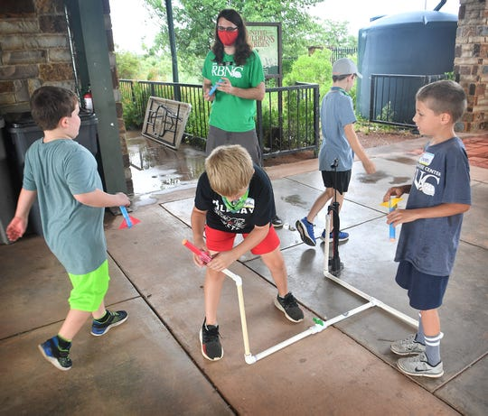 Gabe King, a docent for River Bend Nature Center, supervises as kids prepare to launch the paper rockets they made in the Build It! summer camp Tuesday.