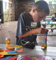 Owen Pickett, 9,  reinforces the nose cone on the paper rocket he made in the Build It! summer camp at River Bend Nature Center.