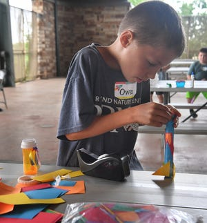 In this file photo, Owen Pickett, 9, reinforces the nose cone on the paper rocket he made in the Build It! summer camp at River Bend Nature Center. This year's camps offer four different sessions with fun activities.