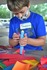 Nathaniel Williams, 8, attaches a set of fins to his paper rocket during the Build It! summer camp at River Bend Nature Center Tuesday.