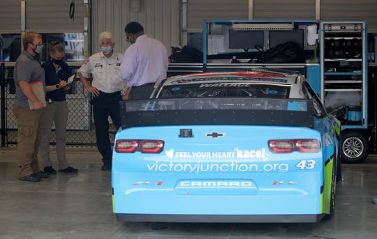 nvestigators speak with personnel in the No. 43 Richard Petty Motorsports garage prior to the NASCAR Cup Series GEICO 500 at Talladega Superspeedway.
