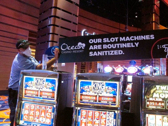 A worker at the Ocean Casino Resort in Atlantic City N.J. installs a sign indicating that slot machines will routinely be sanitized to prevent the spread of the new coronavirus. On Monday, New Jersey Gov. Phil Murphy said Atlantic City's nine casinos can reopen on July 2 at 25% of capacity.